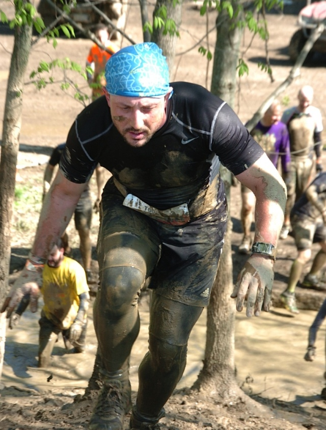 Maurício correndo coberto por lama na Tough Mudder