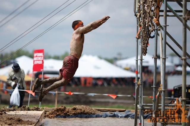 Atleta tentando alcançar obstáculo na Tough Mudder