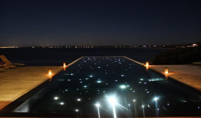 A piscina com borda infinita do Playa Vik fica iluminada à noite