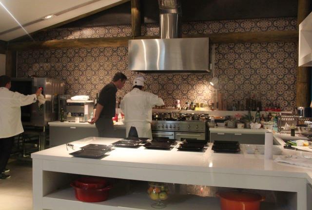 O Chef Guile Kaesemodel e staff trabalhando na cozinha aberta do ambiente